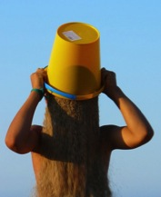 Photo of a person inverting a bucket of sand above her/his head