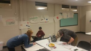 Three students work around a table; one stands over a spiral notebook, reading text; another leans over white paper, sketching; a third sits in a chair, using a laptop. Storyboard appears on wall behind them.