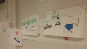 Various large pieces of white paper taped to cinder-block wall; marker-drawn sketches of stick figures (murder victims), hotel rooms, gas stations, and police vehicles