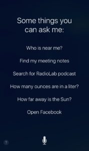 "Screenshot of iOS device showing Siri-suggested questions. ""Some things you can ask me: Who is near me? Find my meeting notes. Search for RadioLab podcast. How many ounces are in a liter? How far away is the Sun? Open Facebook."""